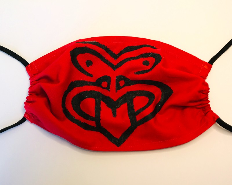 A red mask with a Haka hand printed symbol